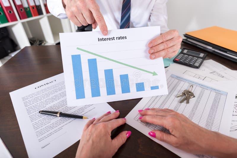 Pośrednik w handlu nieruchomościami pokazuje zmniejszanie stopy procentowe zdjęcie stock