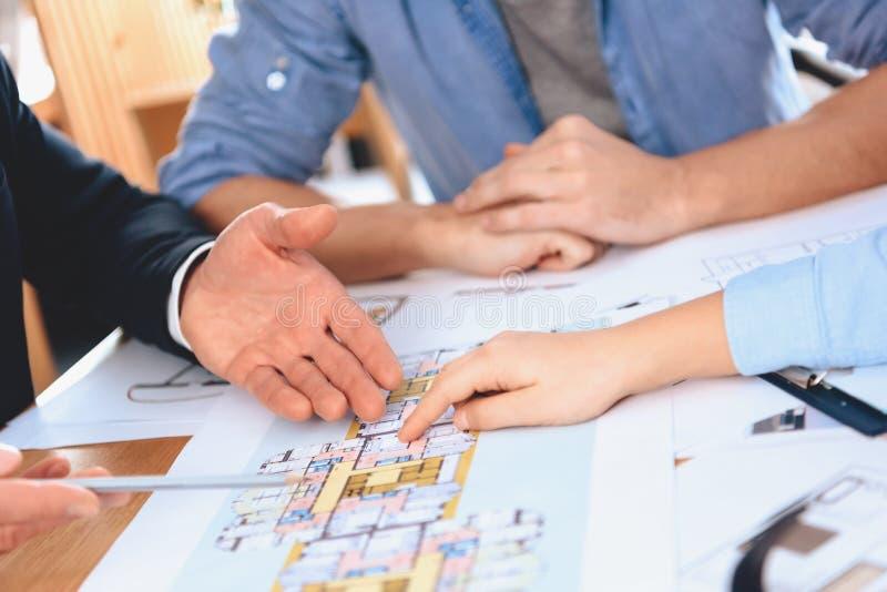 Pośrednika handlu nieruchomościami obsiadanie przy biurkiem w biurze Ojciec, matka i syn, dyskutujemy układ nowy mieszkanie obrazy royalty free