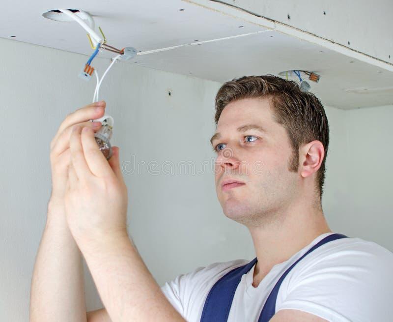 Poświadczający elektryk instaluje żarówkę obrazy royalty free
