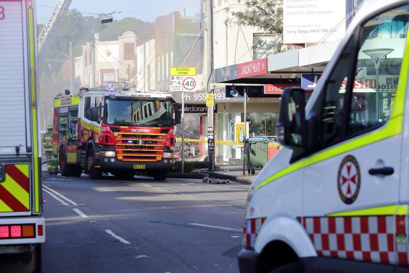 Pożarnicze i ambulansowe załoga uczęszczają sklepowego wybuchu tragadiego zdjęcia stock