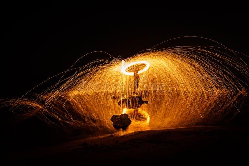Pożarniczej piłki długi ujawnienie używać stalową wełnę przy nocą zdjęcia stock