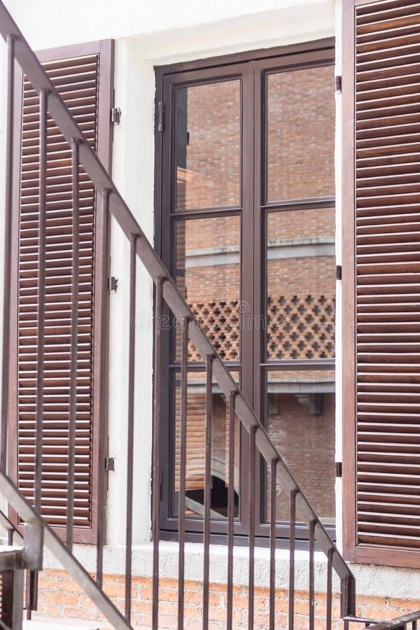 Pożarniczej ucieczki schodki obok okno, ściana z cegieł w szklanym odbiciu niebieski tła architekturę kompasowy głębokie rysunek obraz stock