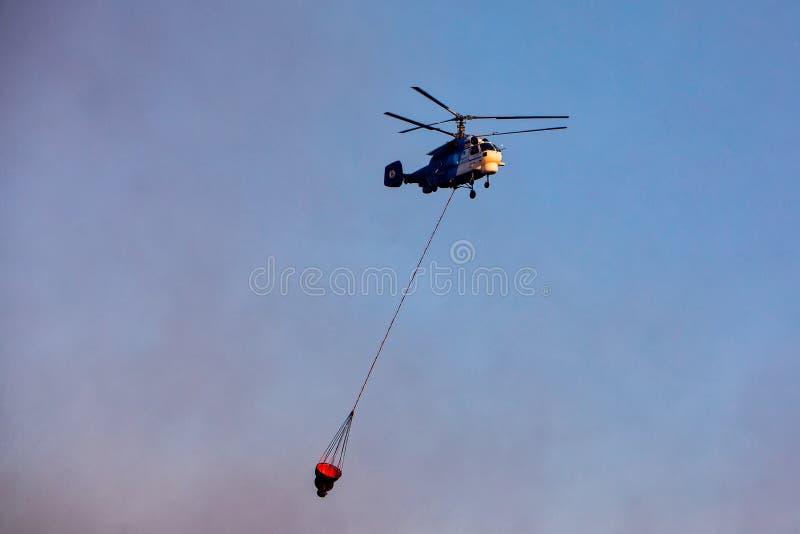 Pożarniczy helikopter z wiadrem woda zdjęcia stock