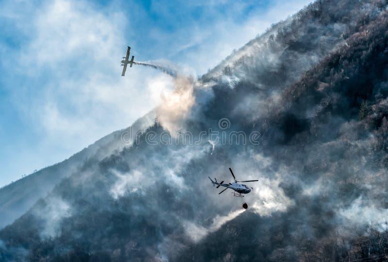 Pożarniczy samolot i helikopter opuszcza wodę dla walczyć ogienia na górze zdjęcie royalty free