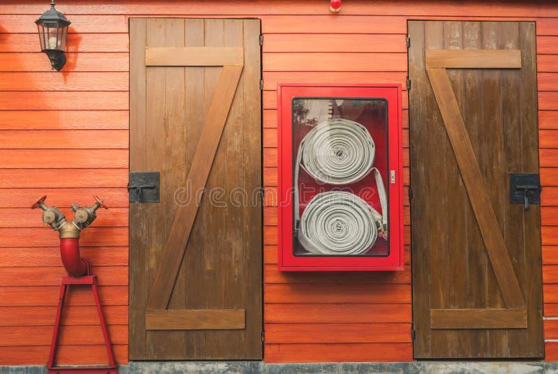 Pożarniczy wąż elastyczny w czerwonym gabinetowym obwieszeniu na pomarańczowej drewnianej ścianie Pożarniczy przeciwawaryjnego wy fotografia royalty free