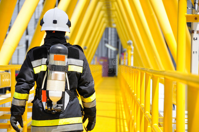Pożarniczy wojownik na ropa i gaz przemysle, pomyślny strażak przy pracą zdjęcie royalty free