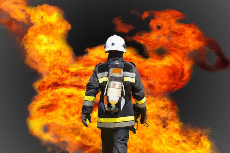 Pożarniczy wojownik na ropa i gaz przemysle, pomyślny strażak przy pracą, Pożarniczy kostium dla wojownika z ogieniem i kostium d zdjęcia stock