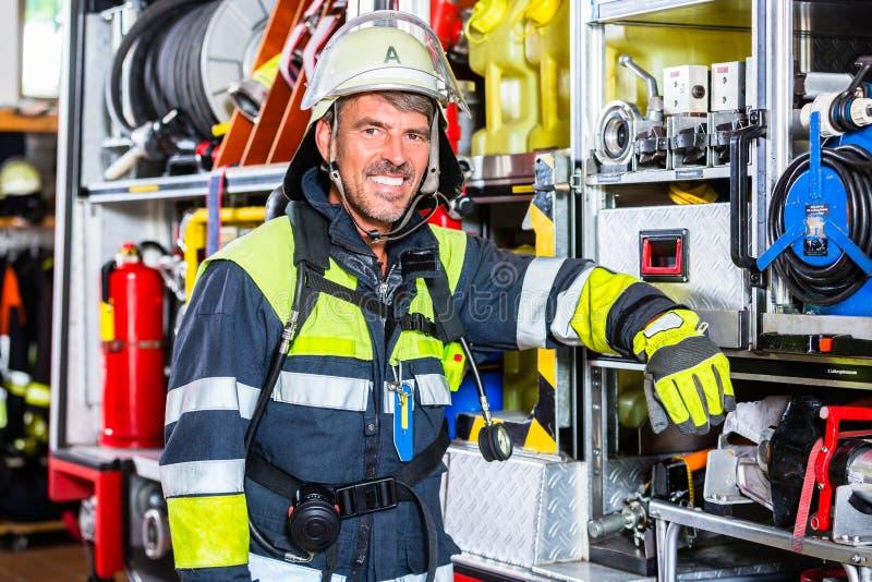 Pożarniczy wojownik w ochronnych ubraniach opiera przy pożarniczym silnikiem obraz royalty free
