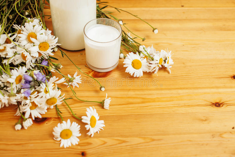 Po prostu elegancka drewniana kuchnia z butelką mleko i szkło na stole, lato kwitnie rumianku, zdrowy foog moring zdjęcie stock