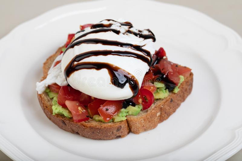 Poached egg on rye toast. Breakfast of poached egg on rye toast with avocado royalty free stock photo
