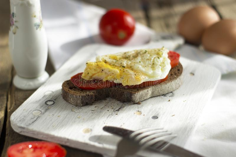 Poached egg on sourdough toast, with grilled tomatoes. A healthy, delicious breakfast or brunch royalty free stock image