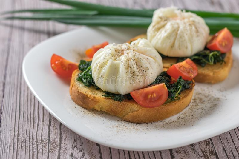 Poached eggs with bread and tomatoes on a plate on a wooden table. royalty free stock images