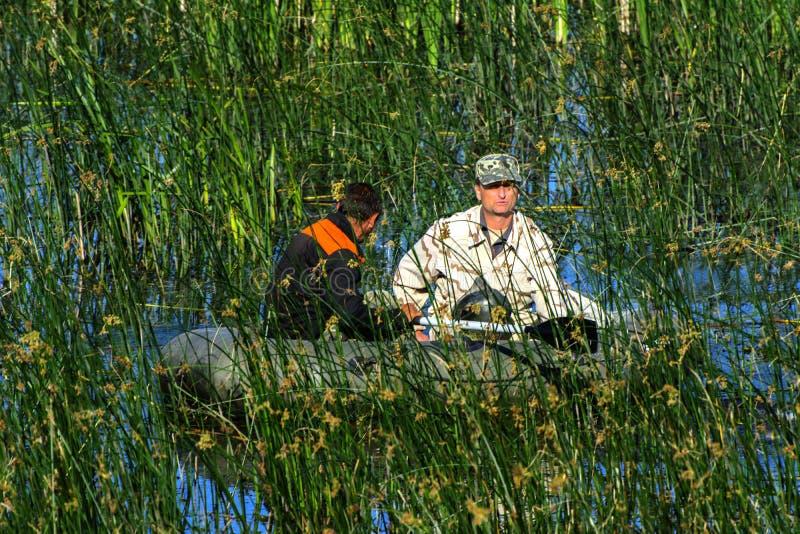 2 poachers на резиновой шлюпке улавливают рыб в сети Zhitomir стоковые фото