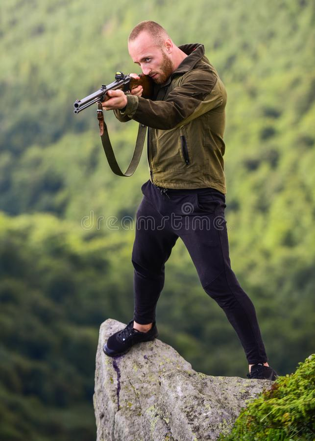 Poaching concept. Poacher stand on edge of cliff. Hunter poacher looking for victim. Hunter with rifle nature stock image