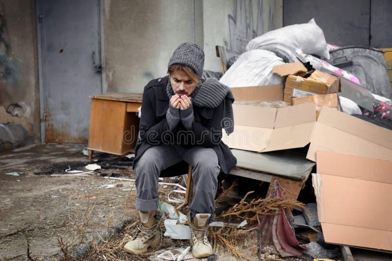 Pobre hombre que se sienta cerca de la basura en la descarga fotos de archivo