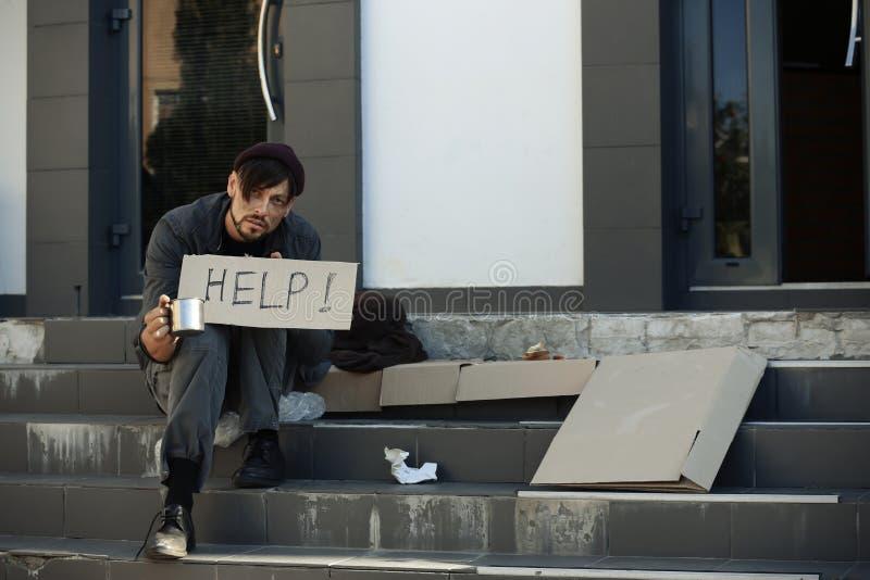 Pobre homem com caneca que implora e que pede a ajuda fotos de stock royalty free
