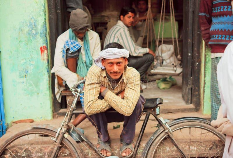 Pobre homem feliz que senta-se com seu ciclo na rua foto de stock