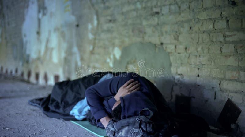 Pobreza, hombre joven sin hogar que duerme en la calle, sociedad egoísta indiferente imagenes de archivo