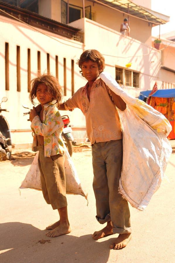 Pobreza & tristeza em toda parte; 2 streetkids uma menina e uma caminhada do menino imagem de stock royalty free