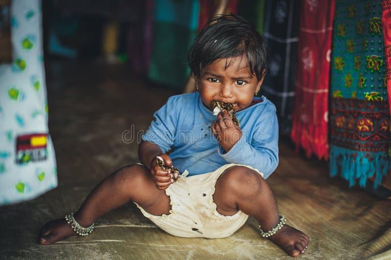Pobreza, uma imagem de uma menina indiana pobre pequena na roupa áspera velha que senta-se no assoalho Bebê do chocolate fotografia de stock