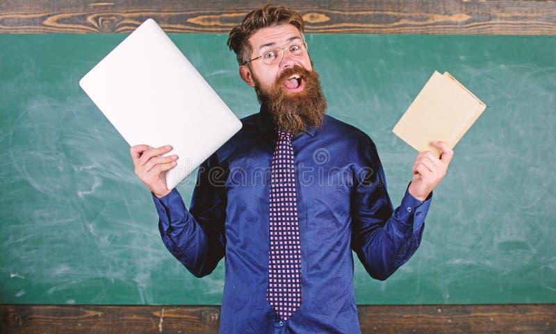 Pobyt nowożytny z technologią Nauczyciela modnisia brodaci chwyty książka i laptop Nowożytna technologii korzyść nauczyciel zdjęcie royalty free
