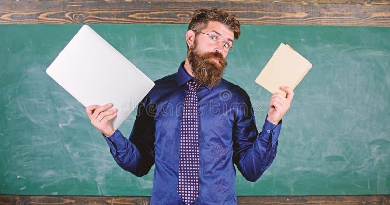 Pobyt nowożytny z technologią Nauczyciela modnisia brodaci chwyty książka i laptop Nowożytna technologii korzyść Digital przeciw zdjęcie stock