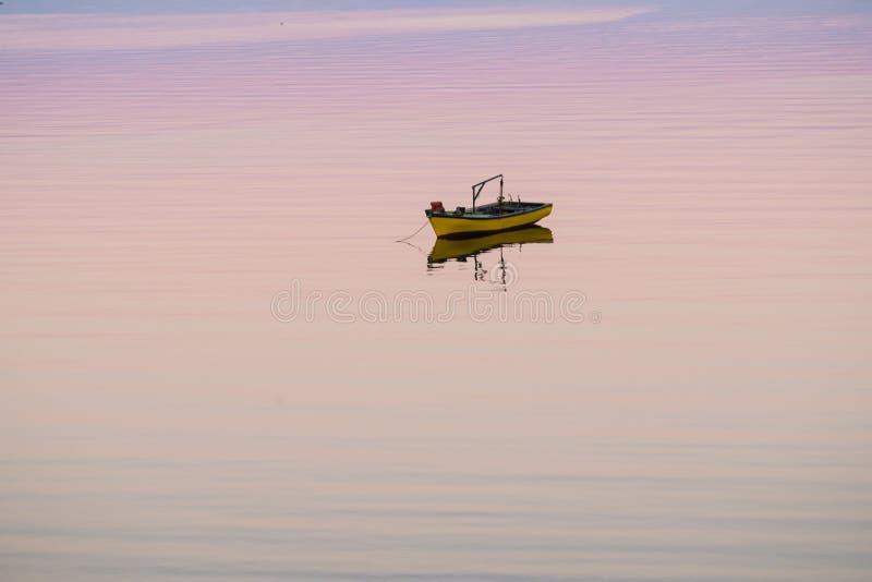 Poca barca che galleggia sul mare fotografia stock