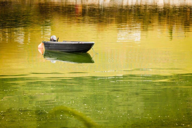 Poca barca sulla superficie dell'acqua fotografia stock
