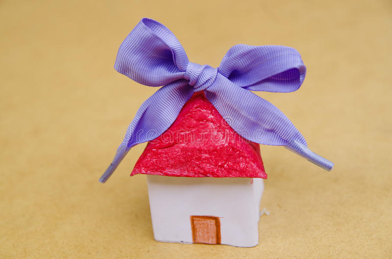Poca bella casa di carta con il nastro porpora su fondo di legno immagine stock