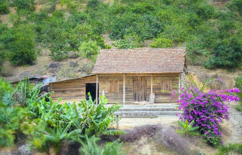 Poca casa en una ladera con las flores de papel adorna imagen de archivo