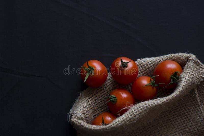 Poca ciliegia del pomodoro sul nero immagine stock