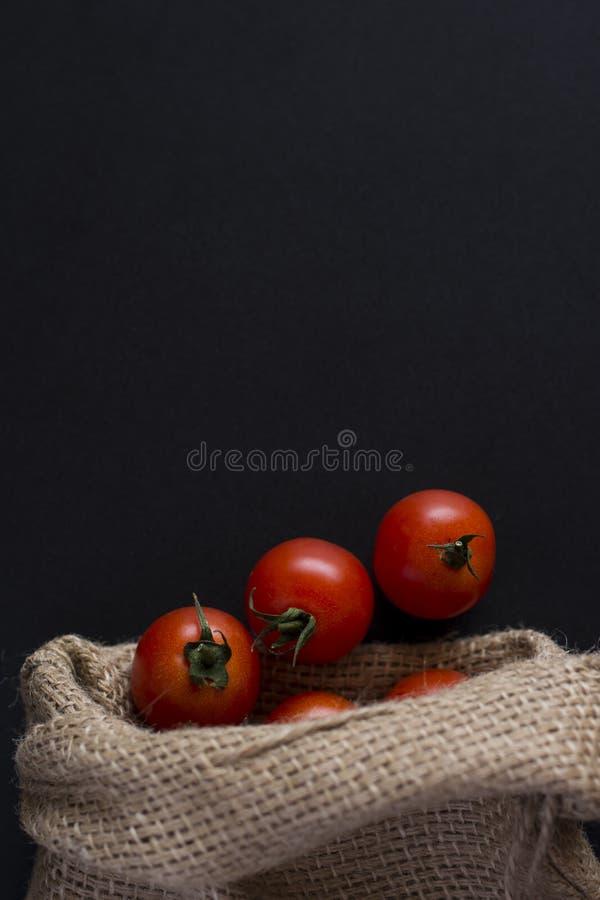 Poca ciliegia del pomodoro sul nero immagine stock libera da diritti