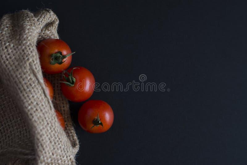 Poca ciliegia del pomodoro sul nero immagini stock