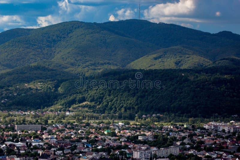 Poca ciudad en un llano entre las colinas verdes de las montañas fotos de archivo libres de regalías