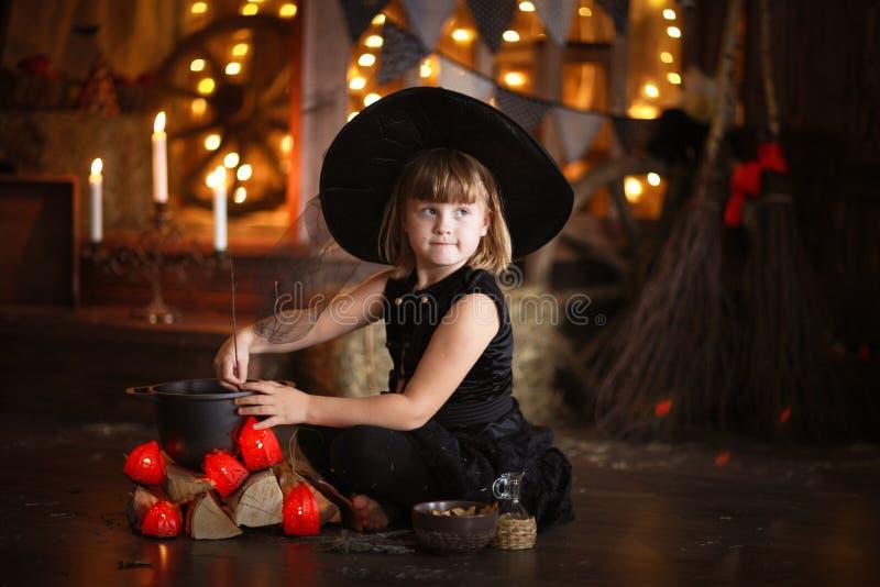 Poca lectura de la bruja de Halloween conjura sobre la niñez h del pote imagen de archivo libre de regalías