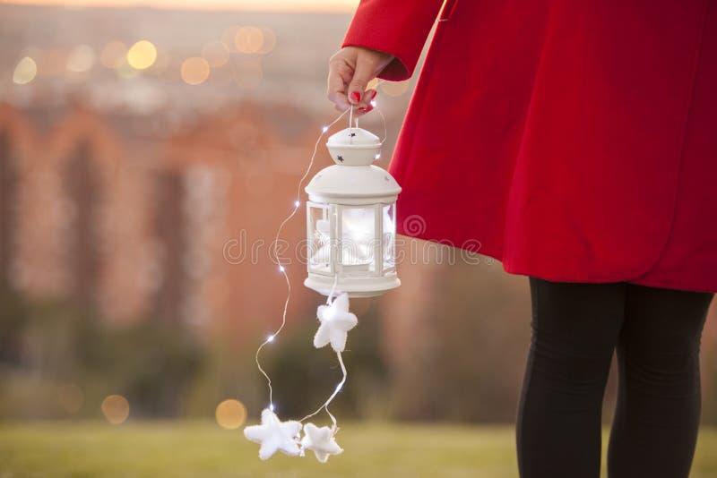 Poca linterna con el control mágico de la iluminación de una mujer en un rojo foto de archivo libre de regalías