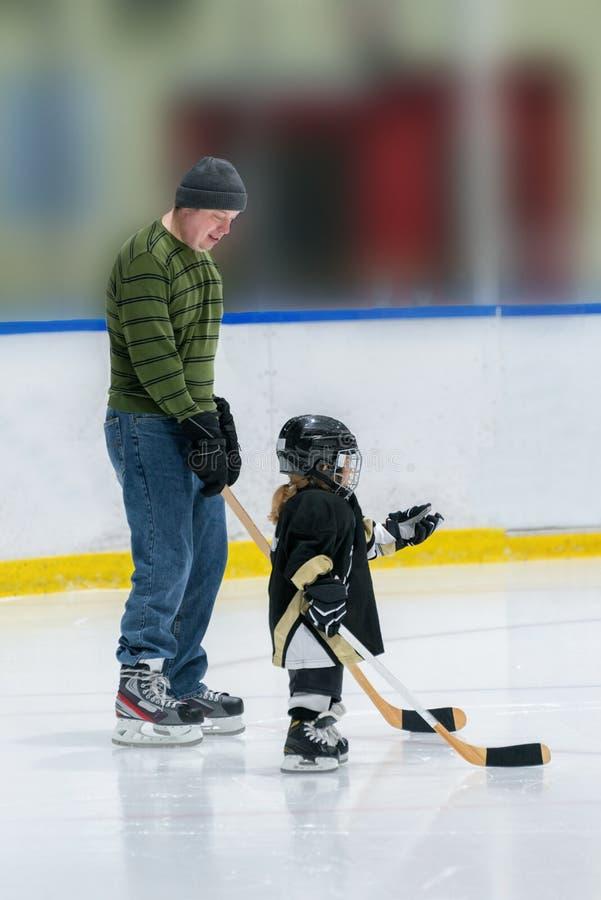 Poca muchacha blanca linda del hockey con el papá en hockey del juego del hielo en el equipo lleno foto de archivo