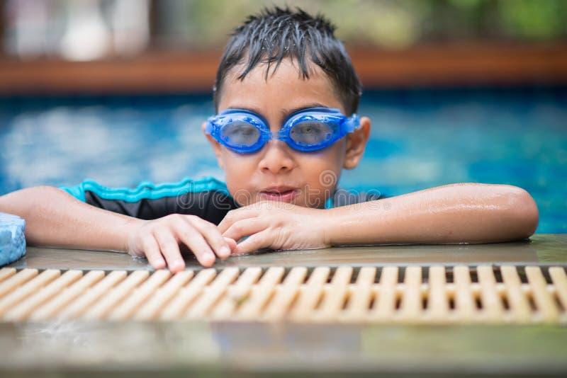 Poca natación árabe asiática del muchacho de la mezcla en la actividad al aire libre de la piscina imagen de archivo