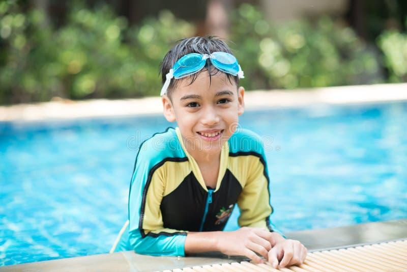 Poca natación árabe asiática del muchacho de la mezcla en la actividad al aire libre de la piscina fotografía de archivo