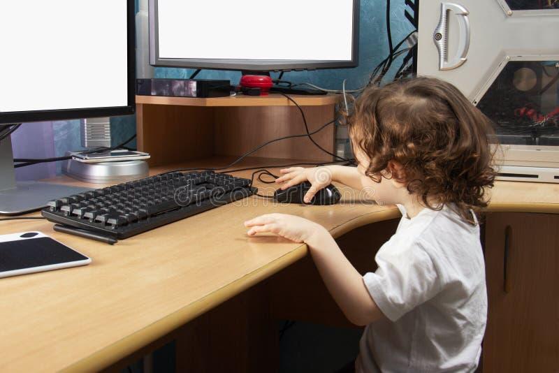 Poca neonata di 3 anni 2 in clothers bianchi disegna al home computer in compressa del disegno di grafici Due videi E immagine stock