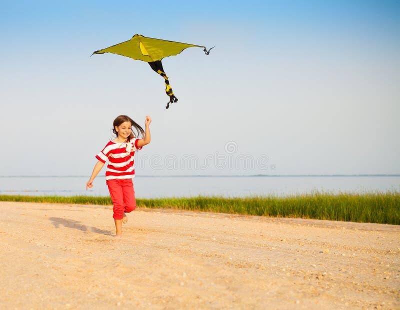 Poca ragazza corrente con l'aquilone di volo sulla spiaggia al tramonto fotografie stock libere da diritti