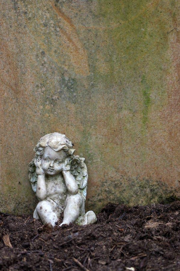 Poca scultura di angelo decora in piccolo giardino fotografie stock