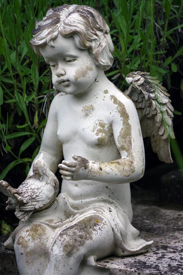 Poca scultura di angelo decora in piccolo giardino immagine stock libera da diritti