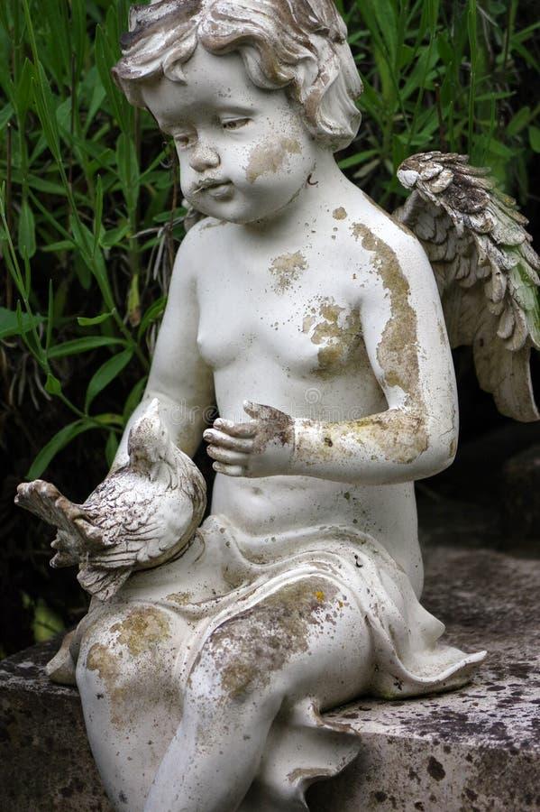 Poca scultura di angelo decora in piccolo giardino fotografia stock