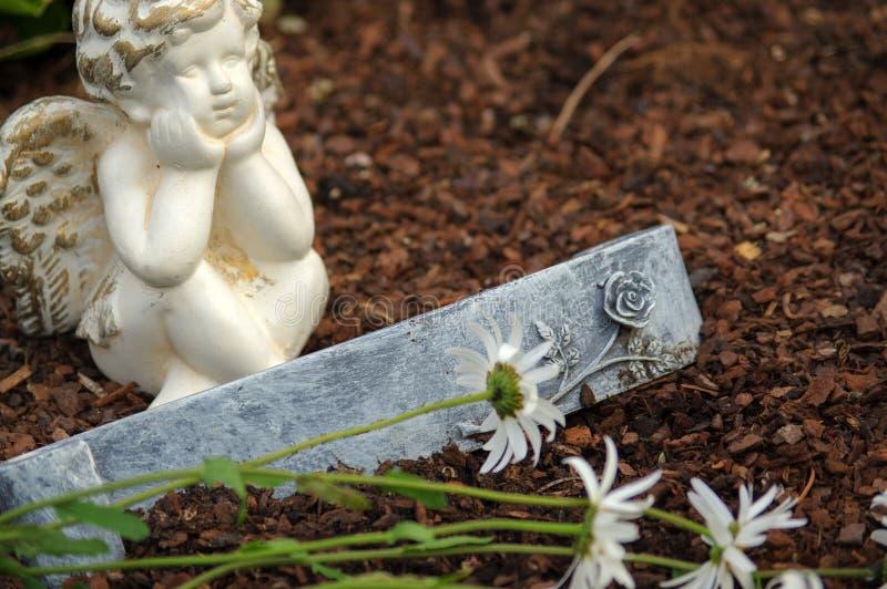 Poca scultura di angelo decora in piccolo giardino con i fiori nella parte anteriore e un segno fotografia stock libera da diritti