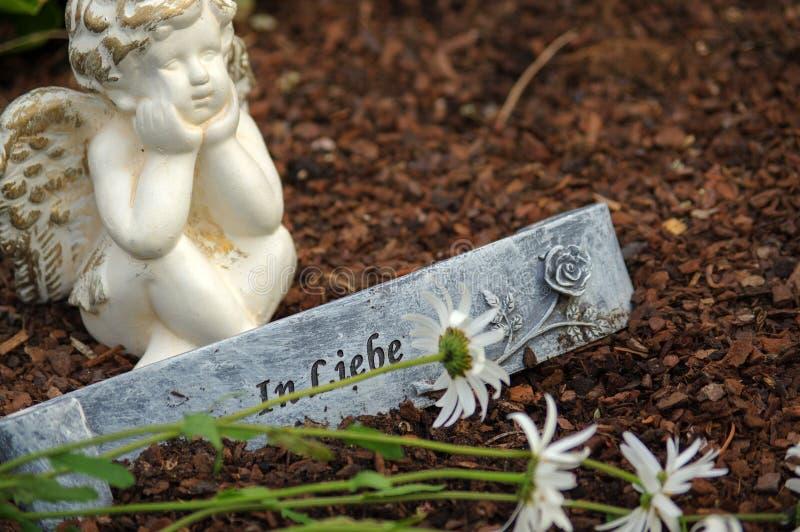 Poca scultura di angelo decora in piccolo giardino con i fiori nella parte anteriore e un segno - nel tedesco dello scambio di co immagine stock libera da diritti