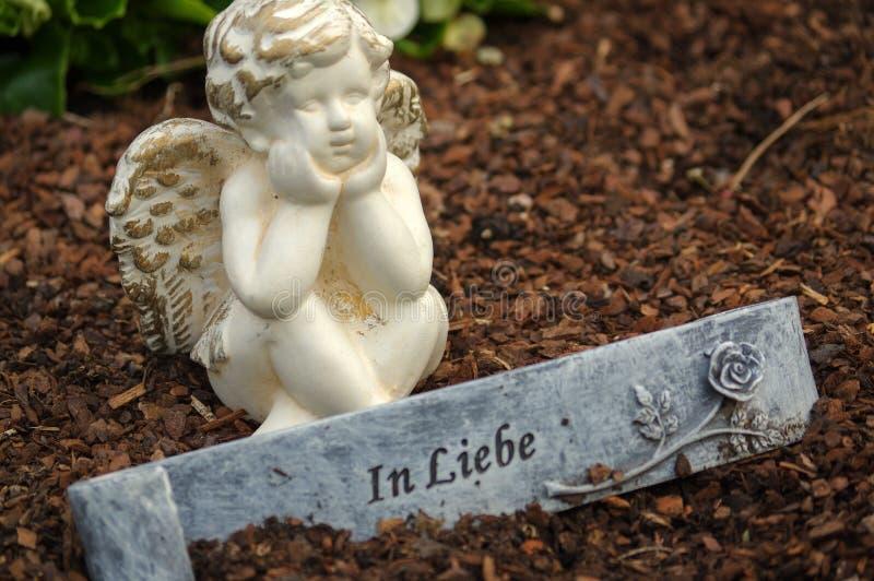 Poca scultura di angelo decora in piccolo giardino con i fiori nella parte anteriore e un segno - nel tedesco dello scambio di co fotografia stock libera da diritti