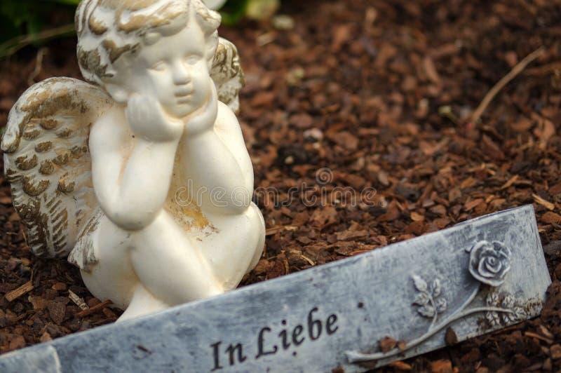 Poca scultura di angelo decora in piccolo giardino con i fiori nella parte anteriore e un segno - nel tedesco dello scambio di co immagine stock