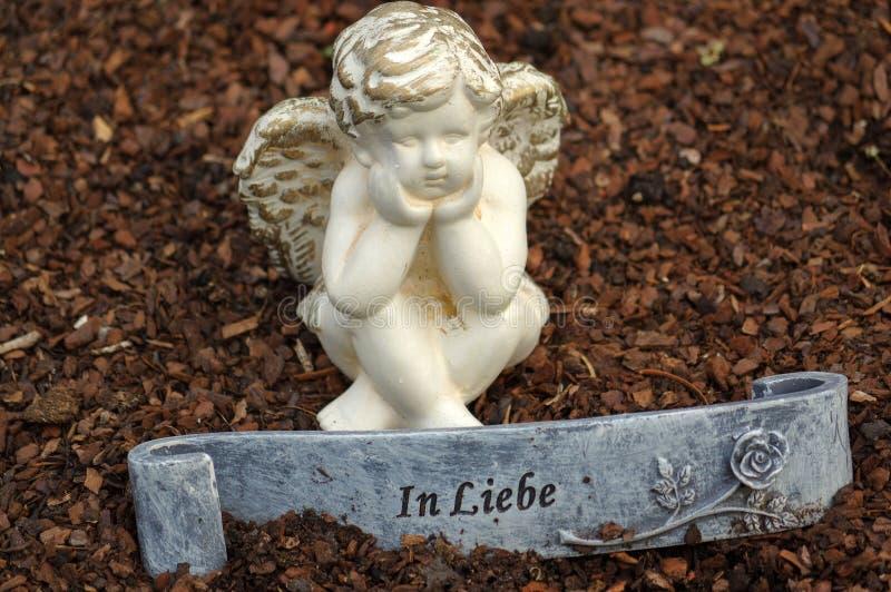 Poca scultura di angelo la decora in piccolo giardino con un segno nella parte anteriore - nel tedesco dello scambio di complimen fotografie stock