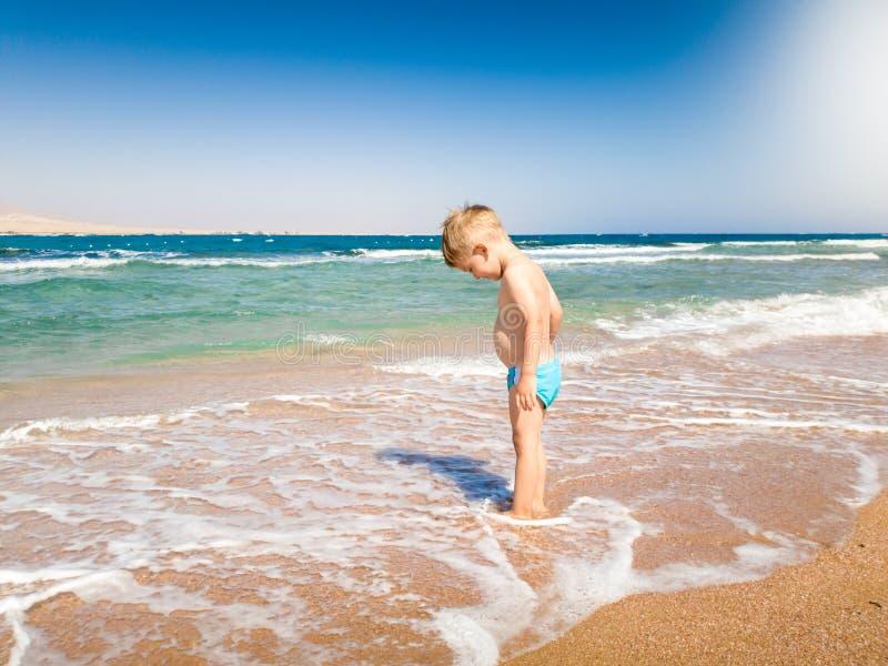 Poca situación del niño pequeño de 3 años en ondas del mar tranquilo y mirada en sus pies Ni?o que relaja y que tiene buen tiempo foto de archivo libre de regalías
